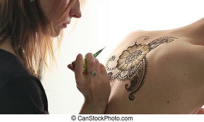 Mehndi artist making pattern on model's back - Mehndi artist...