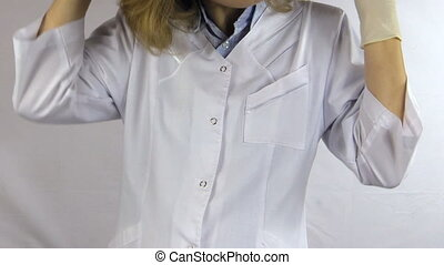 woman doctor gloves - Woman doctor in white robe smock put...