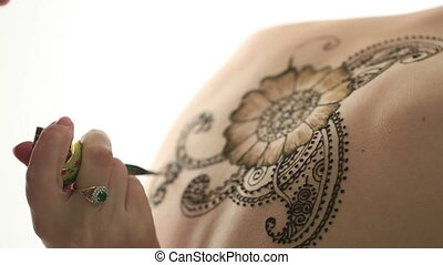 Close-up of mehandi artists hand drawing pattern - View of...