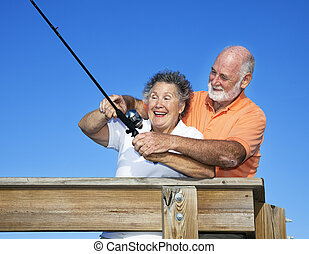 Fishing Lessons - Senior woman getting a fishing lesson from...