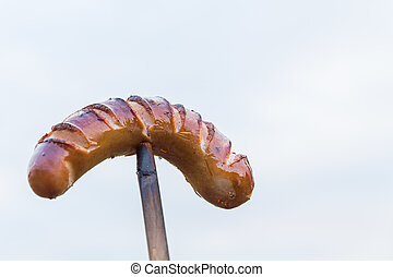 sausage on a wooden stick against cloudy sky