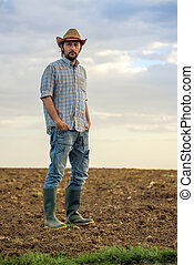 Male Farmer Standing on Fertile Agricultural Farm Land Soil...