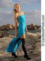 Woman in long dress on the rocks
