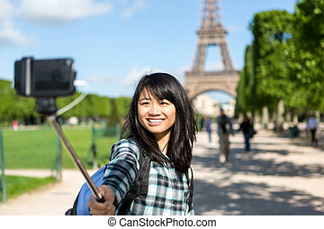 Young attractive asian tourist in Paris taking selfie - View...