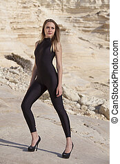 Model in black catsuit and spiked heels