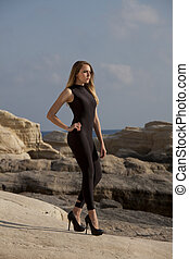 Woman in black catsuit by sunset