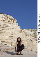 Woman in black catsuit on the rocks