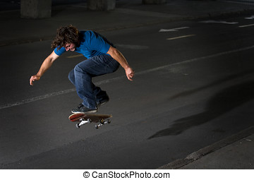 Skateboarder doing a flip on street at night