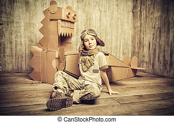 airman - Cute dreamer boy playing with a cardboard airplane...