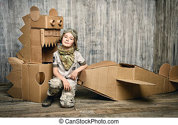 skyman - Cute dreamer boy playing with a cardboard airplane...
