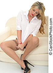 Beautiful Sexy Attractive Young Woman Sitting on A Sofa in a White Shirt Stockings and High Heel Shoes