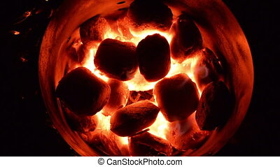 Coal Heating - A top view of red hot coals heating up in a...