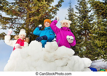 Group of kids play snowballs game together standing behind...