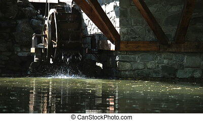 Decorative watermill wheel in motion outdoors