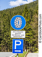 snow chain sign with parking place to change in the alps