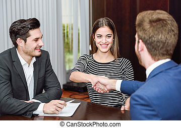 Smiling young couple shaking hands with an insurance agent...