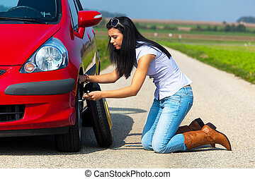 Young Woman Changing Tire - Young woman crouched down and...