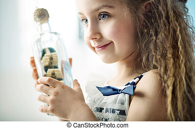 Little girl holding a bottle with a ship - Little kid...