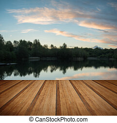 Summer vibrant sunset reflected in calm lake waters with wooden planks floor