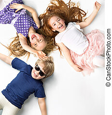 Portrait of siblings lying on a white background - Portrait...