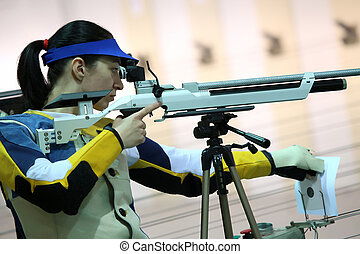 woman aiming a pneumatic air rifle - beautiful young woman...