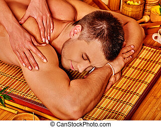 Man getting bamboo massage - Handsome man getting massage in...