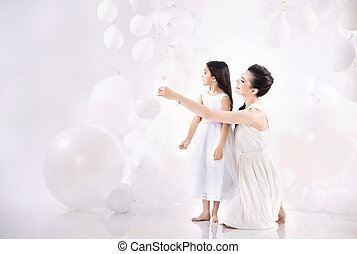 Mom and daughter playing balloons - Mom and cute daughter...