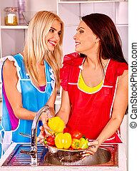 Women washing fruit at kitchen. - Happy women washing...