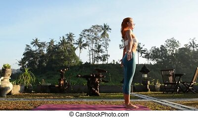Young woman practicing yoga salutation greeting the sun at...