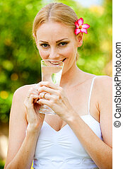 Drinking Water - An attractive woman drinking a glass of...