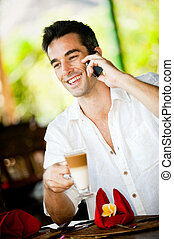 Man With Drink And Phone - An attractive caucasian man with...