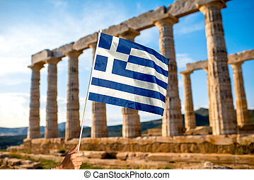 Greek flag on Poseidon temple background in Sounion, Greece
