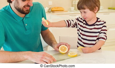 Son and dad eating lemon together