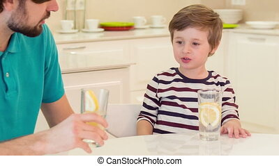 Dad and son sitting in kitchen - Do you want my water...