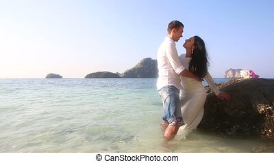 bride and groom stand in sea leaning on rock
