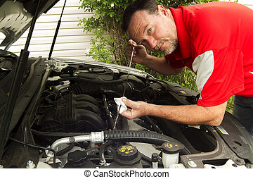 A Mechanic Checking The Oil In A Car
