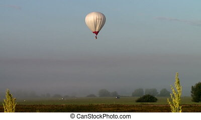 View of hot air balloon landing at field
