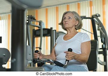 Senior woman exercising in a gym