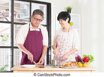 asian senior couple cooking at the kitchen