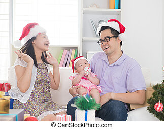 asian parents celebrating christmas with baby
