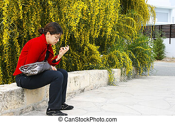 Girl at the mimosa tree - Pretty brunette girl sitting at...