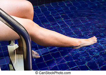 Soaking feet in water for relaxing on the swimming pool