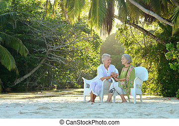 Elderly couple sitting on a beach - Beautiful elderly couple...