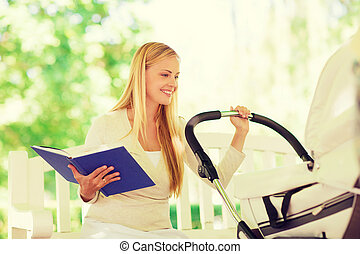 happy mother with book and stroller in park - family, child,...