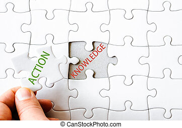 Missing jigsaw puzzle piece with word ACTION - Hand with...