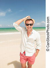 Happy young man walking on the beach