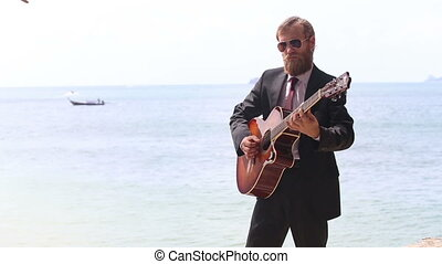 european man plays guitar against sea islands and boat -...