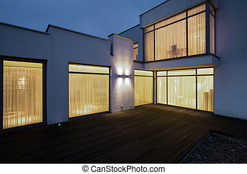 House at night - Big modern house with wooden porch at night