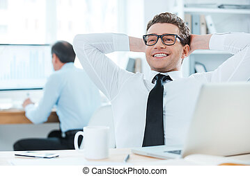 Satisfied with the work done. Cheerful businessman in formalwear holding head in hands while sitting at his desk in the office