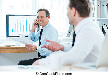 Well done! Two cheerful business people in formalwear discussing something and smiling while sitting in the office